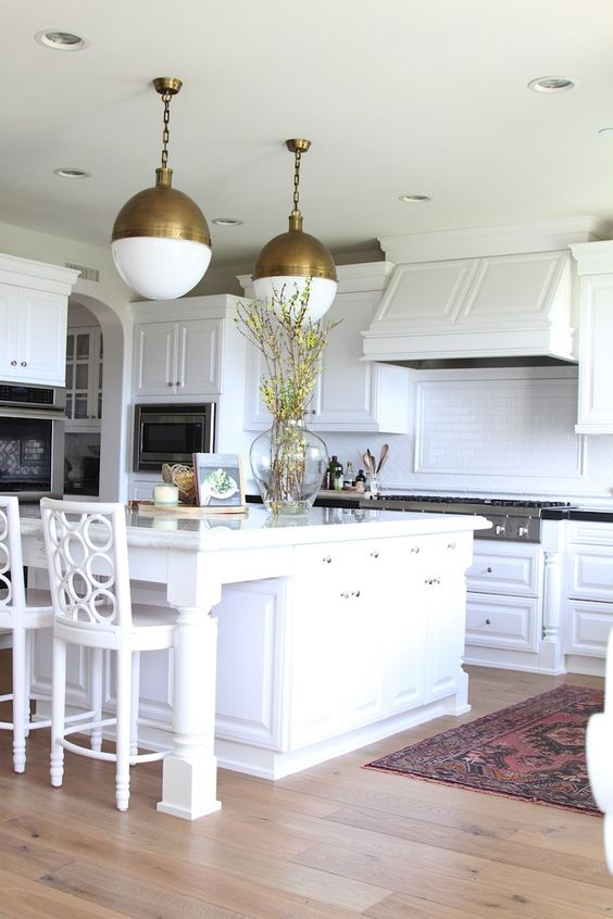 warm wood floors for an all-white kitchen and ceramic tile backsplash