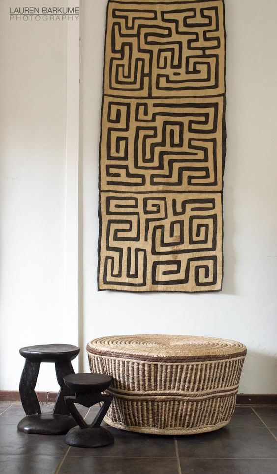 A woven table and wooden stools amde by African artisans and the Kuba cloth
