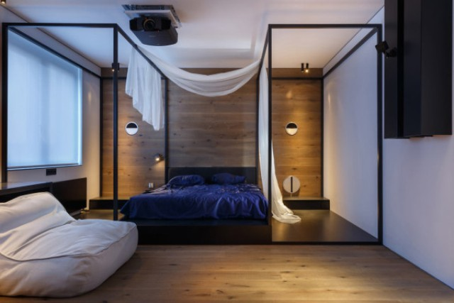 The bedroom features a wooden wall behind the bed and two metal structures that are almost like opposite canopies