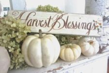 12 white pumpkins and a sign