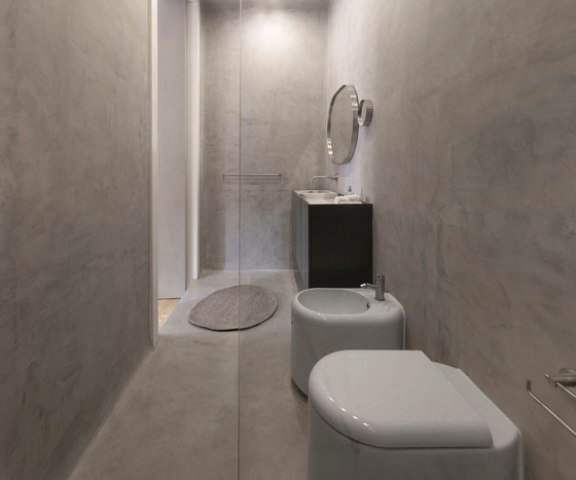 The bathroom is small, clad with marble-inspired tiles
