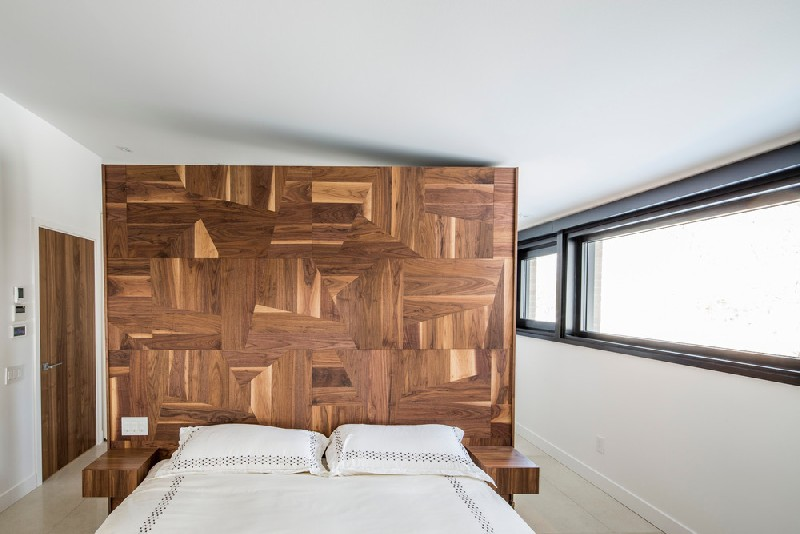 The bedroom can also boast of a statement wall but this one is made of geometrically clad wood