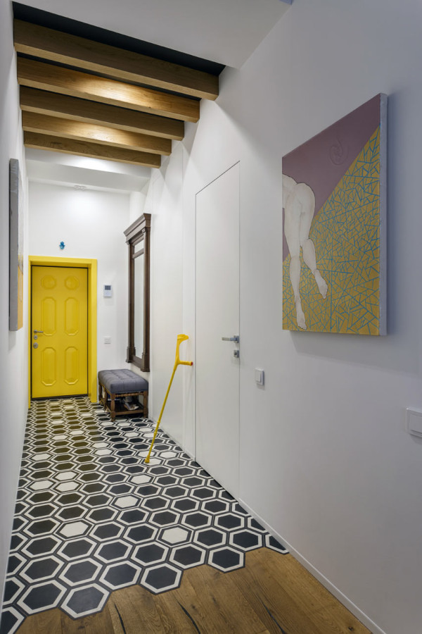 The hallway is bold and colorful, with creative geo tiles and the owner's art piece