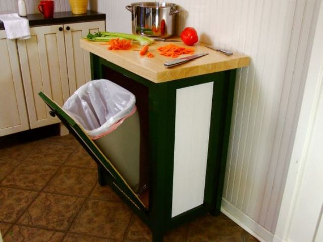 a kitchen trash can cabinet with a tilt open door