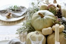13 white pumpkins in a wooden tray, grey napkins and pinecones