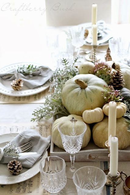 white pumpkins in a wooden tray, grey napkins and pinecones