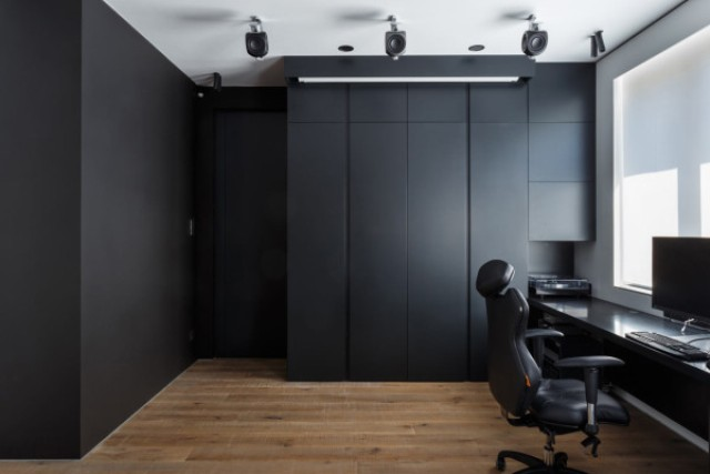 The home office is clad with dark panels, which hide everything until the owner needs it