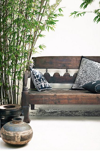 a worn carved dark wood bench with dark pottery for outdoors