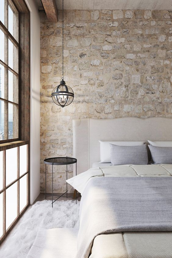 airy chic bedroom with stone clad that looks antique and adds a refined touch