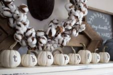 14 pumpkins with letters and a cotton wreath
