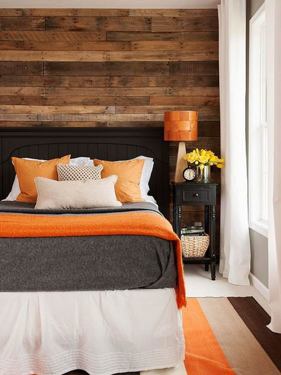 warm wood and orange accents make this bedroom inviting and positive