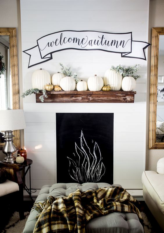 faux mantel with pumpkins and a fabric wall decoration