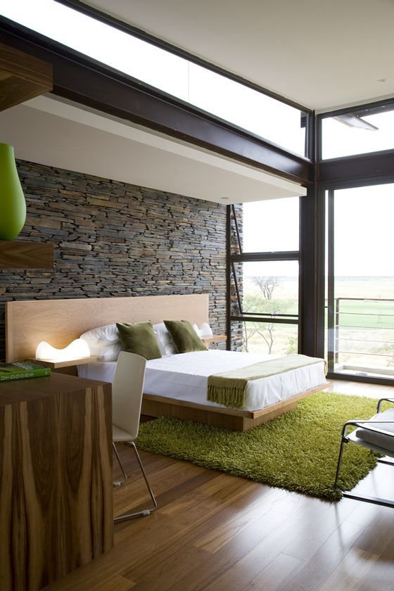 ultra-modern bedroom with a stone wall that gives texture to the room