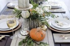 19 natural pumpkins, greenery and large candles on a fabric table runner