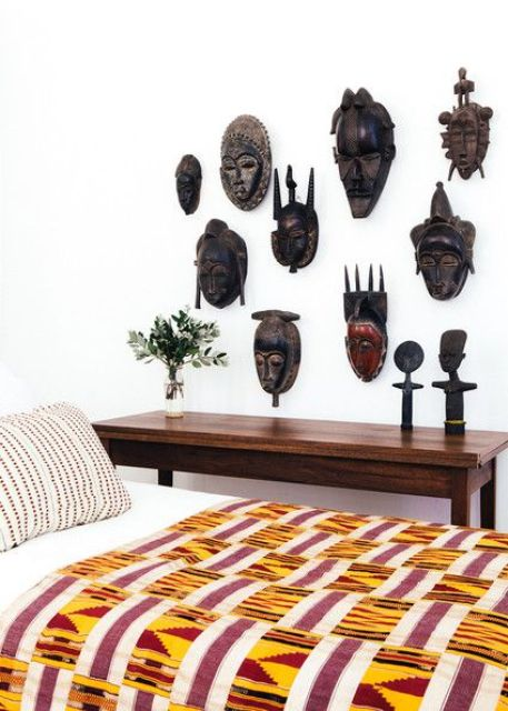 A collection of African carved masks on a bedroom wall for a statement