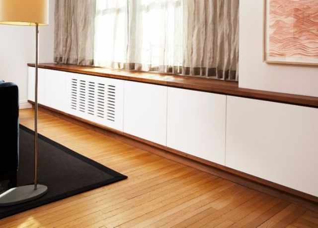 white and natural wood radiator cover attached to the window sill