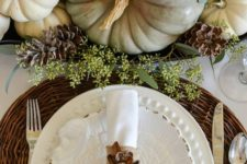21 fall pumpkins, pinecones and greenery centerpiece, a woven charger and a pinecone napkin ring