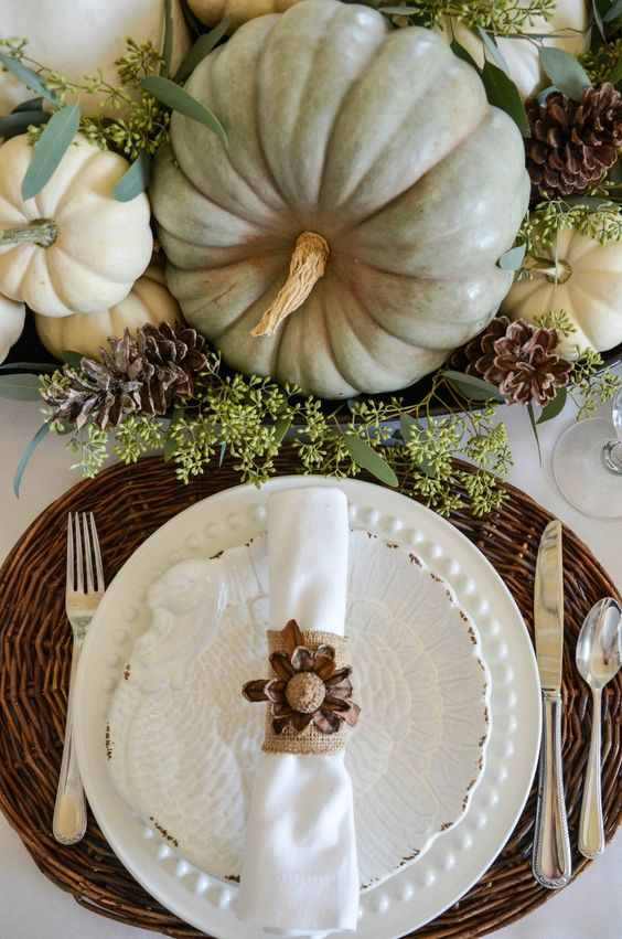 fall pumpkins, pinecones and greenery centerpiece, a woven charger and a pinecone napkin ring