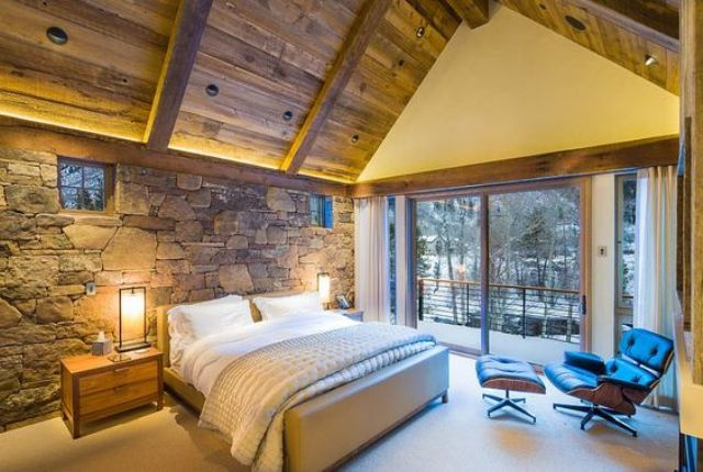 natural stone headboard wall and a wooden ceiling