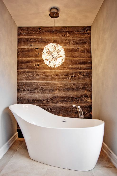worn wood wall contrasts with a modern bathtub and chandelier