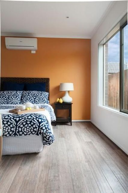 light brown flooring soothes the orange accent wall