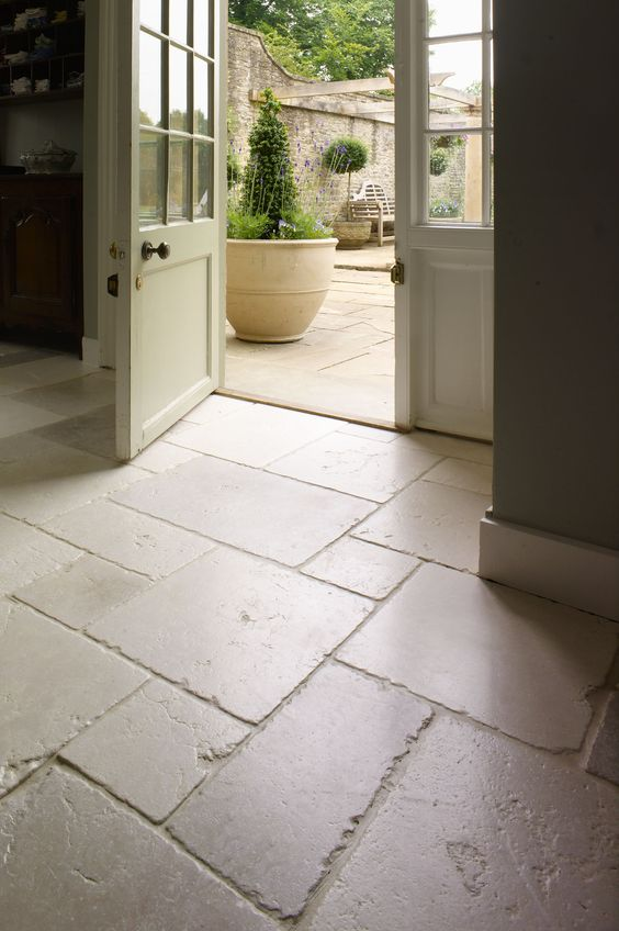 beautifully aged limestone floors in the entryway and outdoors to connect spaces