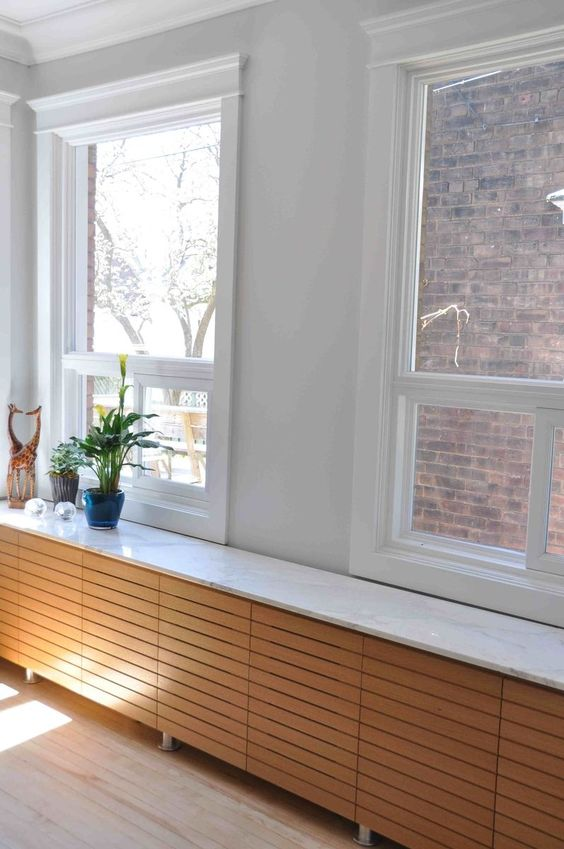 wooden radiator cover that serves as a window sill and a display shelf