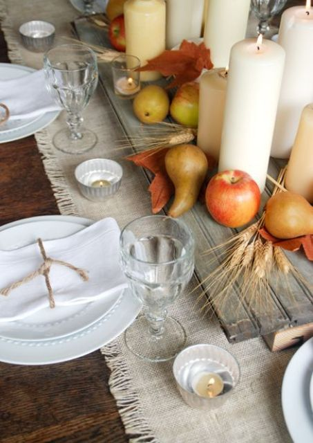 board with apples, pears and candles on a fabric table runner