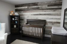 25 nursery with a reclaimed wood wall behind the bed for a rustic feel