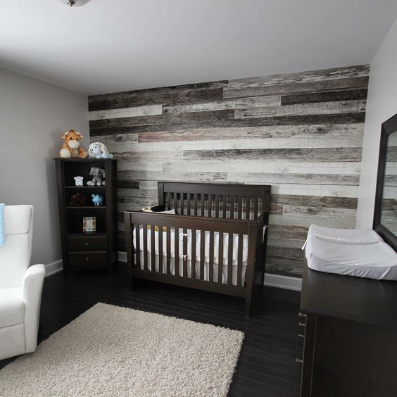 nursery with a reclaimed wood wall behind the bed for a rustic feel