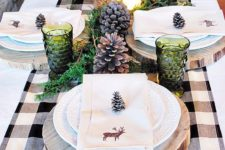 27 green glass candle holders, pinecones, wood slice chargers and greenery