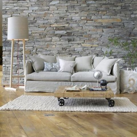 grey stone wall behind the sofa accentuates this area
