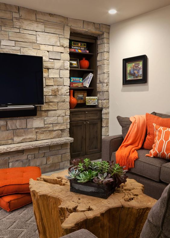 stacked stone accent wall and petrified wood coffee table bring texture and interest to the neutral space