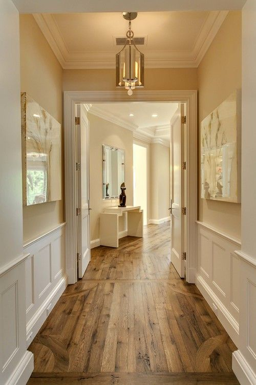 weathered wood floors with molding and cream color walls