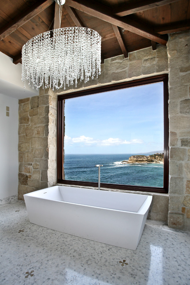 Antique stone wall looks amazing in a contemporary luxurious bathroom. It amazingly frames sea views. (Ancient Surfaces)