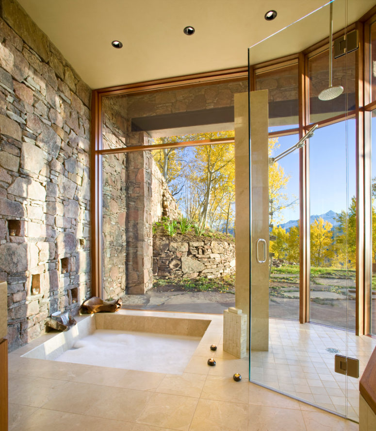 Full height glass and natural stone wall link the bathroom with the landscape around the house. (RKD Architects, Inc)