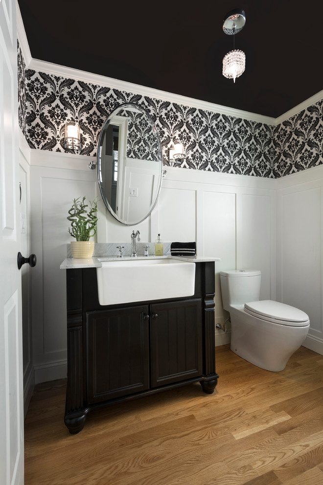 Tall white wainscoting creates strong contrast with a black ceiling in this traditional powder room.