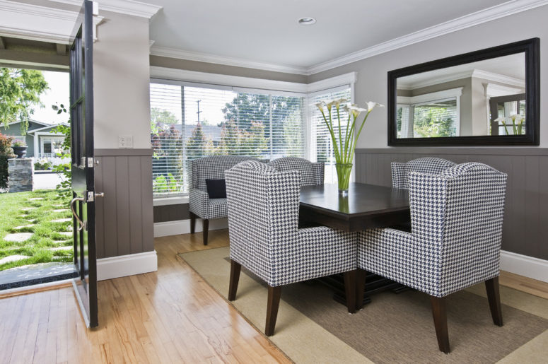 Dark grey wainscoting creates dimension and contrast in this dining area.