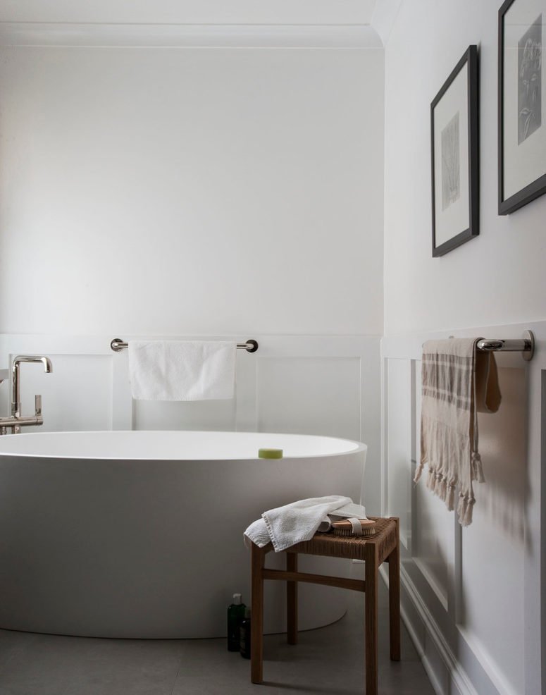 Water resistant wainscoting is a perfect addition to a modern plain white bathroom. (indi interiors)