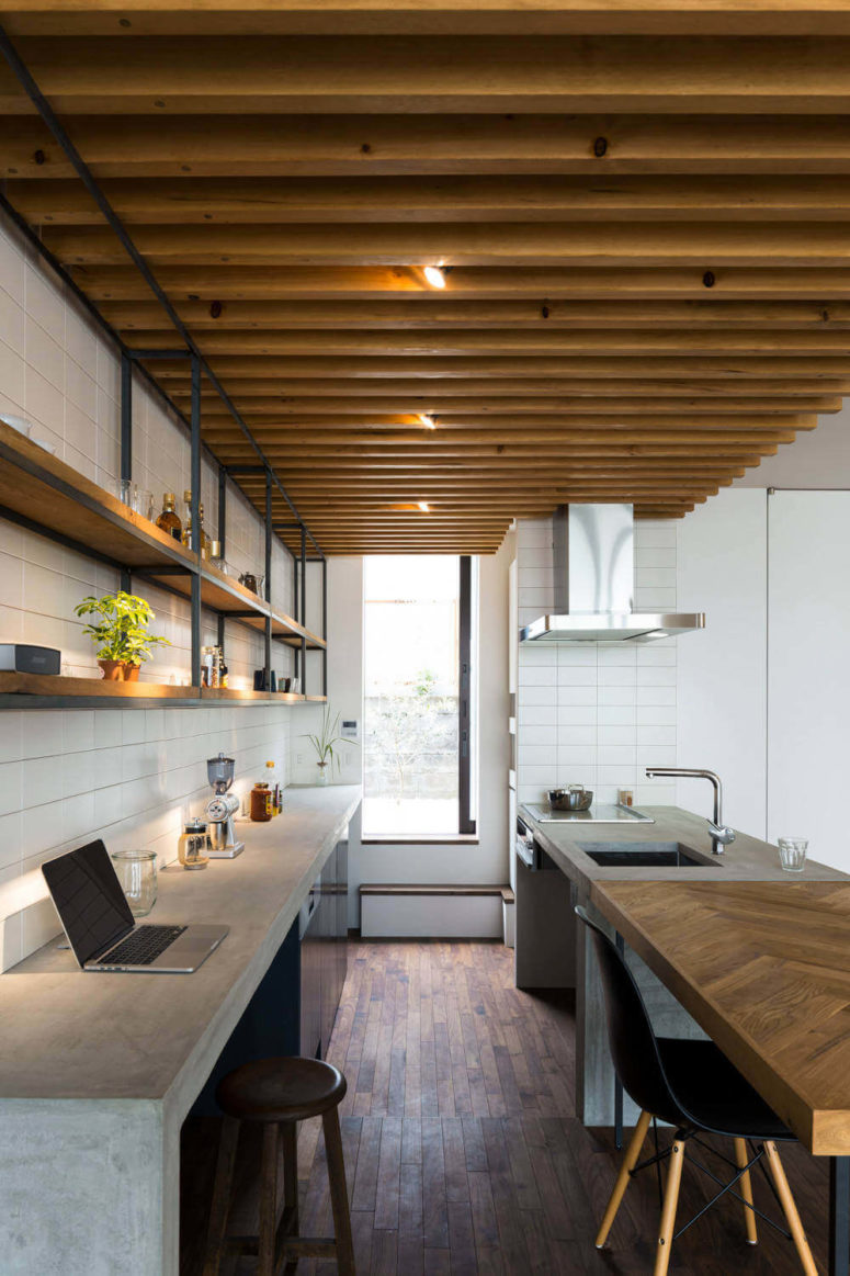The kitchen is decorated with concrete and warm natural woods