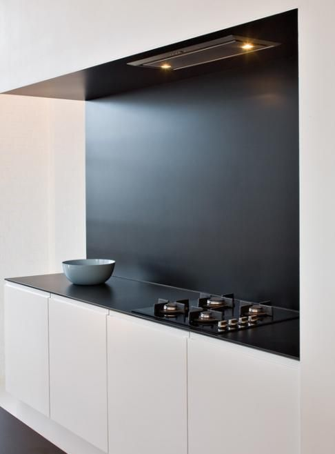 minimal kitchen with contrasting accents and built in cabinets for a sleek clean look