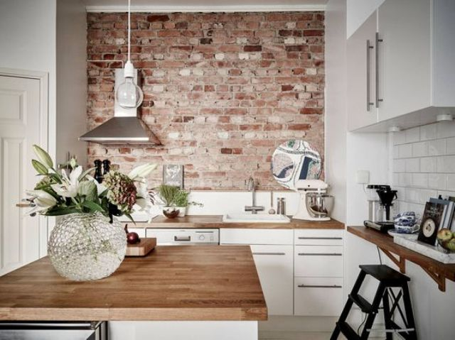 Rough Brick Wall Creates A Bold Accent In This Modenr White Kitchen And Makes It Look
