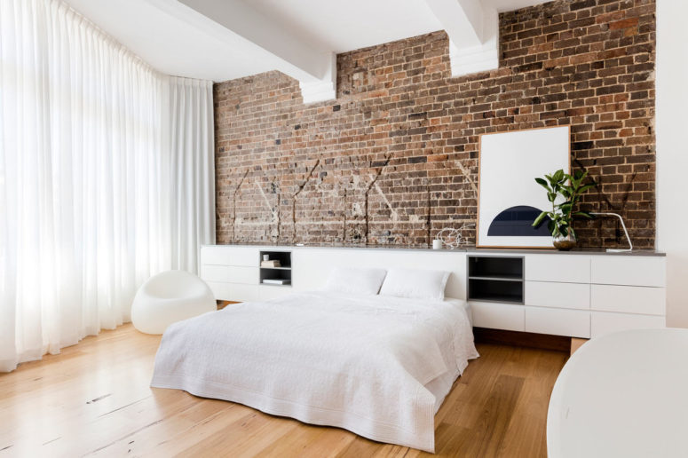 An exposed brick wall in the bedroom is softened with white furniture and textiles