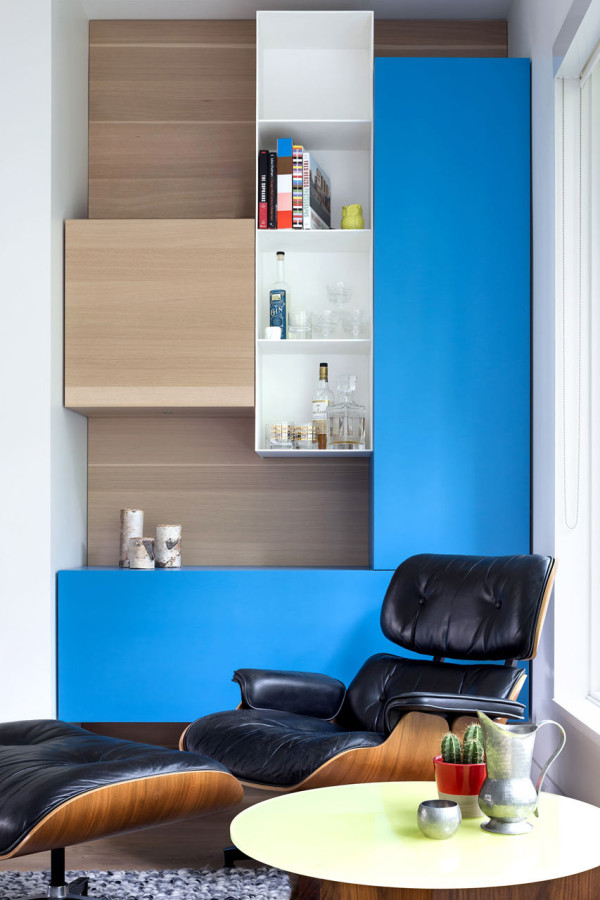 This bold relaxing nook by the window is accentuated with a blue unit and a small home bar