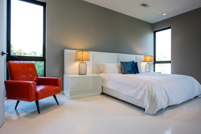 The bedroom is decorated in minimalist style with just a couple of bold accents