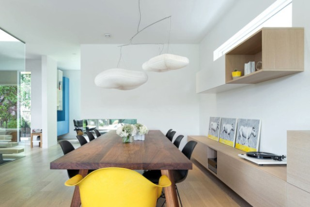 The dining space is unique with its cloud lamps, rich-colored wooden table and sunny yellow accents