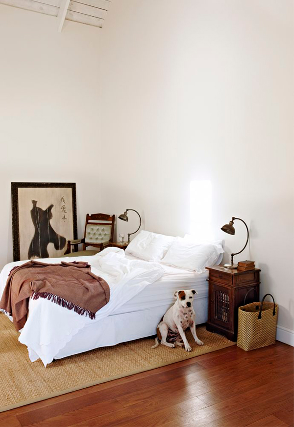 The master bedroom is very simple, with just a comfy bed, vintage nightstands and lamps and a jute rug for a textural look