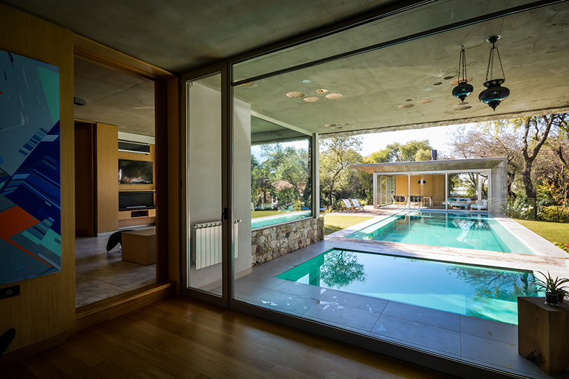 a pool is positioned between the two structures, bordered by wooden decking