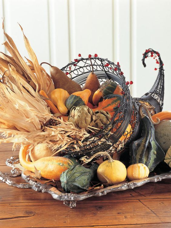 metal cornucopia centerpiece with vegetables, corn husks and wheat inside