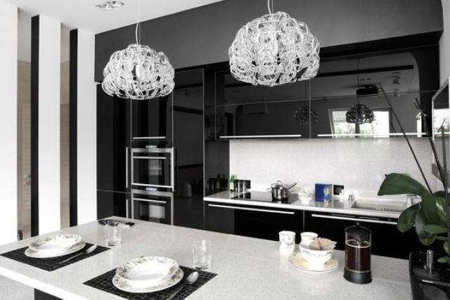 modern black and white kitchen with dual crystal pendant lights, white counter tops, and black high gloss laminate cabinets